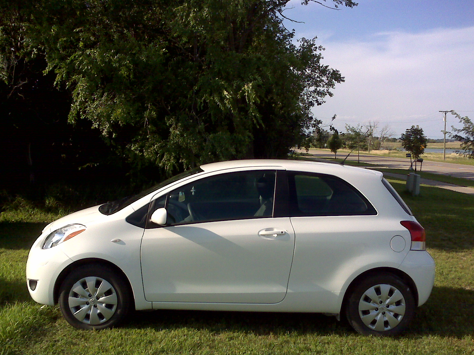 Photograph of a white 2010 2-door Toyota Yaris hatchback.